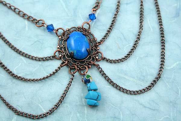 Blue howlite brass decollete necklace, on blue, md
