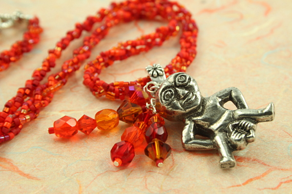Sheela-na-gig fertility necklace, red, orange, earth, wave, md