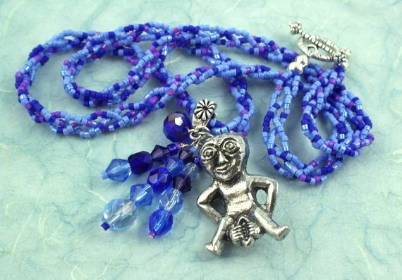 Sheela-na-gig necklace - purple and blue, heap left, md