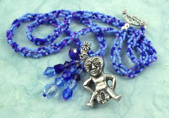 Sheela-na-gig necklace - purple and blue, heap left, md
