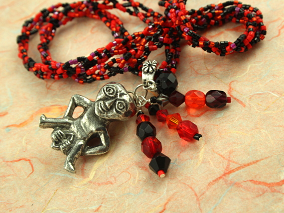 Sheela-na-gig necklace - red and black, closeup, md